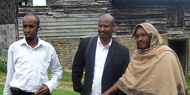 Somalis from Ocean Somali Community Centre in London pose in front of barns